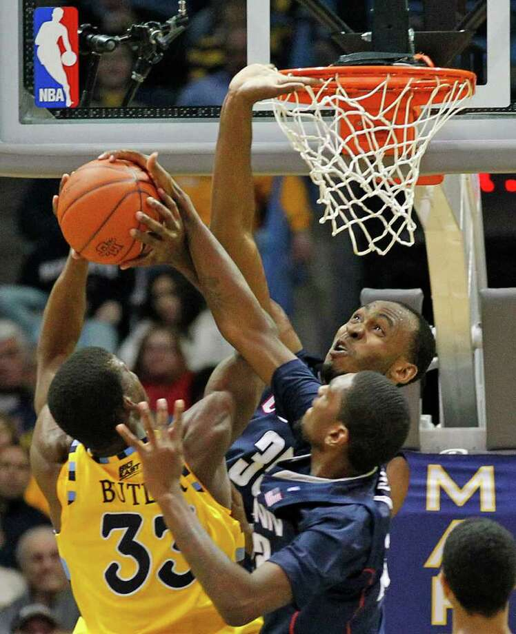 Connecticut's Charles Okwandu (35) and Roscoe Smith (22) defend against Marquette's Jimmy Butler (33) in the second half of an NCAA college basketball game Tuesday, Jan. 25, 2011, in Milwaukee. (AP Photo/Jeffrey Phelps) Photo: AP