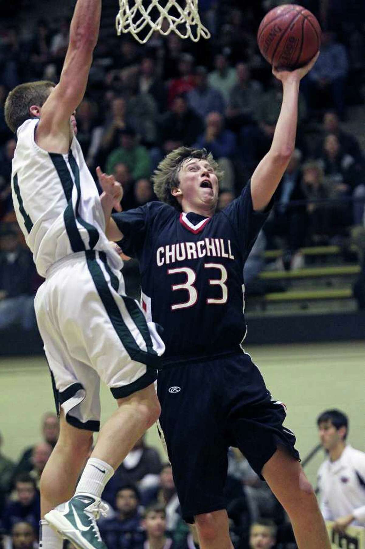 Churchill's Jacob Woods gets a shot off around Max Yon as the Reagan boys play Churchill at Littleton Gymnasium on Tuesday, Jan. 25, 2011. Churchill won 96-84.