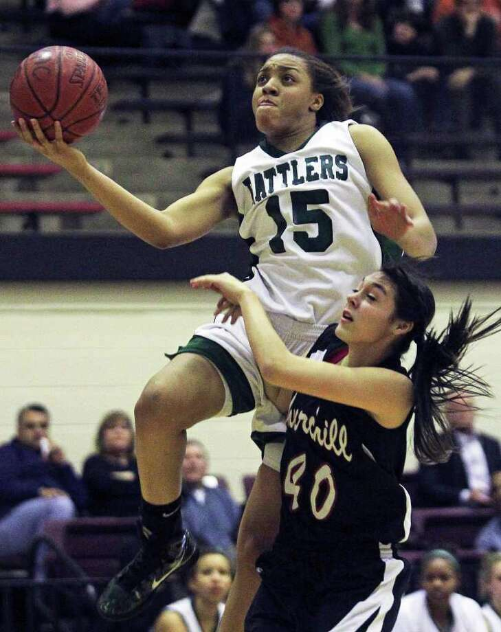 Rattlers forward Sabrina Berry puts up a layup in the second half against Rebecca Flores as the Reagan girls play Churchill at Littleton Gymnasium on Tuesday, Jan. 25, 2011. Reagan won 53-44. Photo: TOM REEL, SAN ANTONIO EXPRESS-NEWS / © 2010 San Antonio Express-News