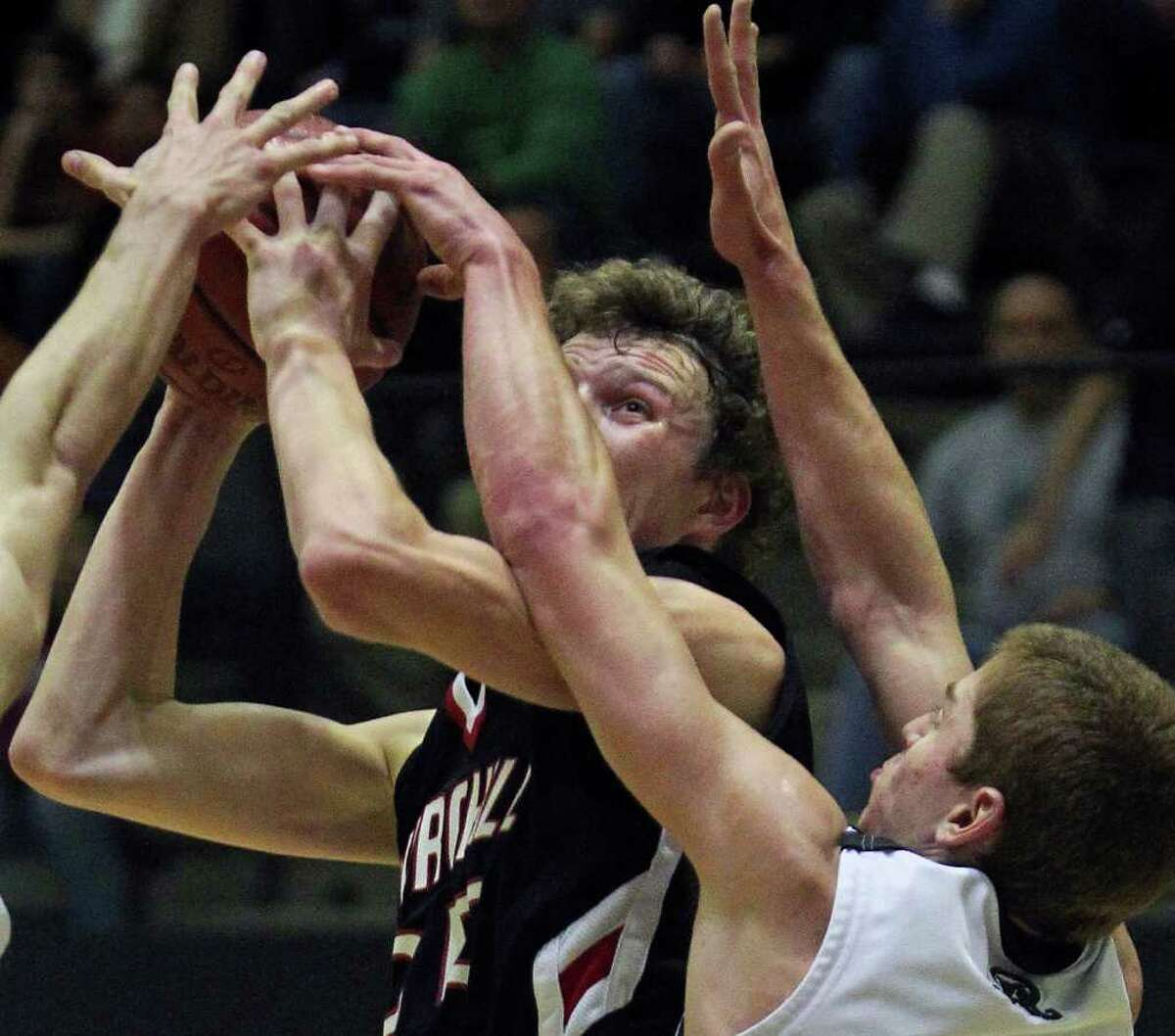 Chargers forward Clark Lammert goes up and draws a foul on Max Yon as the Reagan boys play Churchill at Littleton Gymnasium on Tuesday, Jan. 25, 2011. Churchill won 96-84.