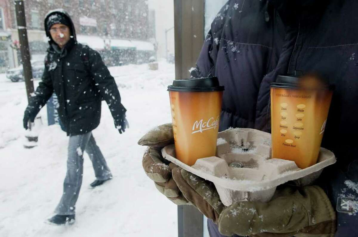 Commuters wait for the bus with coffee in hand downtown as more snow blankets the area in Stamford, Conn. on Wednesday January 26, 2011.