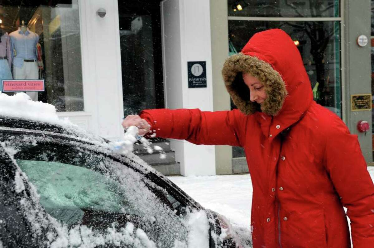Kim Aanonsen, of Greenwich, brushes snow off her car on Greenwich Avenue, in Greenwich, on Wednesday, Jan. 26, 2011.