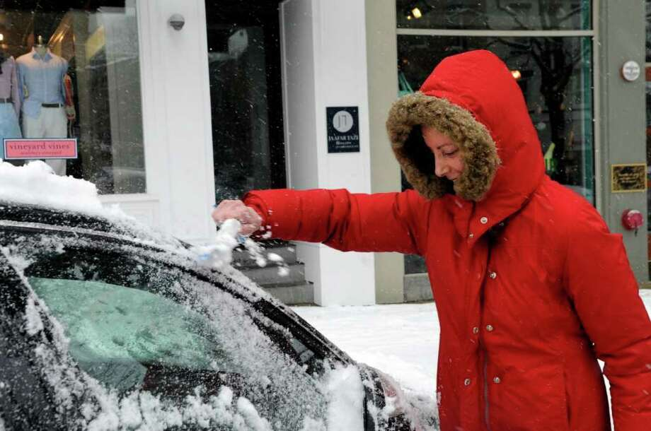 Kim Aanonsen, of Greenwich, brushes snow off her car on Greenwich Avenue, in Greenwich, on Wednesday, Jan. 26, 2011. Photo: Helen Neafsey / Greenwich Time