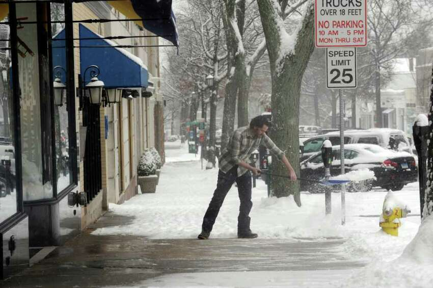 James Burgess, manager of Rugby, shovels snow in front of the store on Greenwich Avenue, in Greenwich, on Wednesday, Jan. 26, 2011.