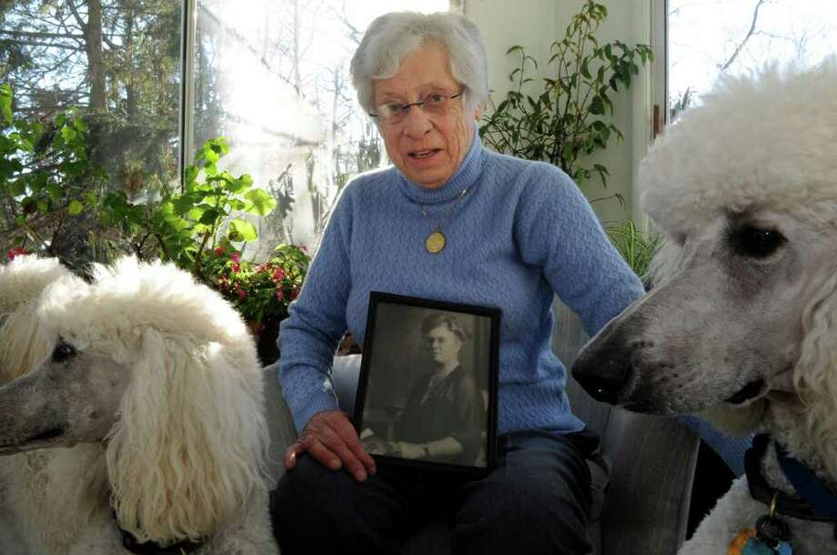 Percy Lee Landstaff, a former president of the state League of Women Voters, holds a photograph of her grandmother, Josephine Hamilton Maxim, who was one of the founding members of the Connecticut League, as she sits in her home in Stamford, with her standard poodles, from left, Ticey, Tori, and Perrier, on Monday, Jan. 24, 2011. Photo: Helen Neafsey / Greenwich Time