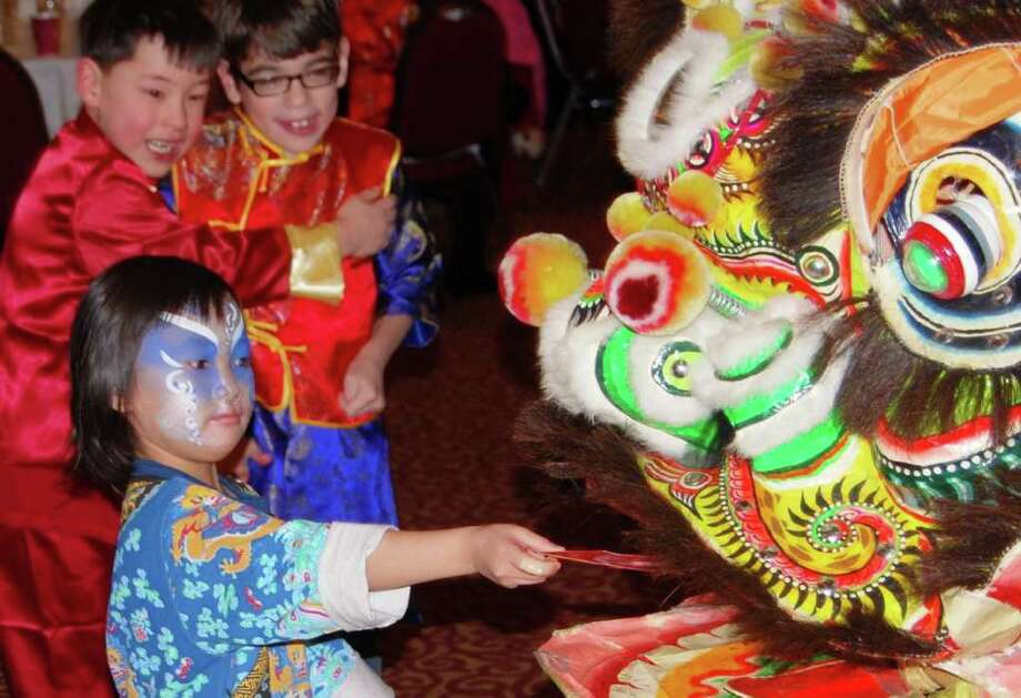 "Nancy Kessler, 4, feeds the festival's colorful lion a traditional red envelope containing ""hong-bao,"" or good luck money, a Chinese New Year tradition to thank the lion for warding off evil spirits and bringing prosperity in the New Year. Photo: Julie Ruth / Greenwich Citizen"