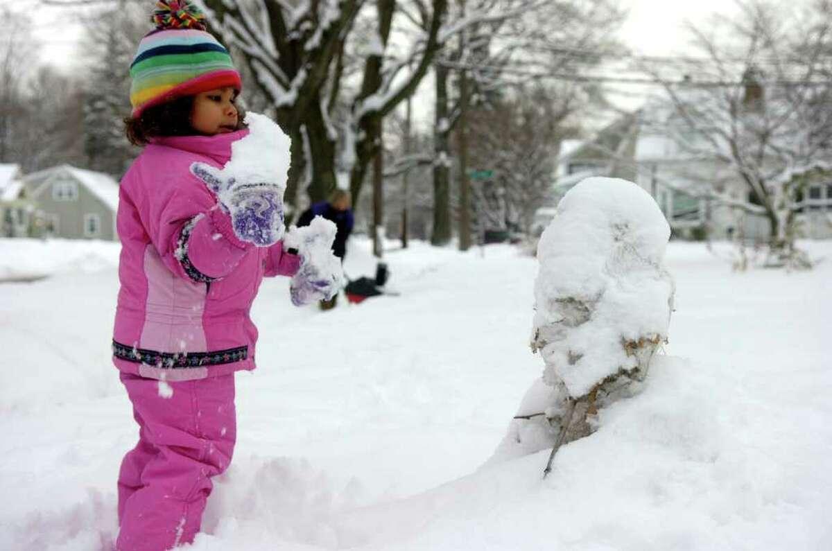 Alexandra Lockwood, 2, gives a snowman a little extra fluff in Fairfield on Wednesday, January 26, 2011.