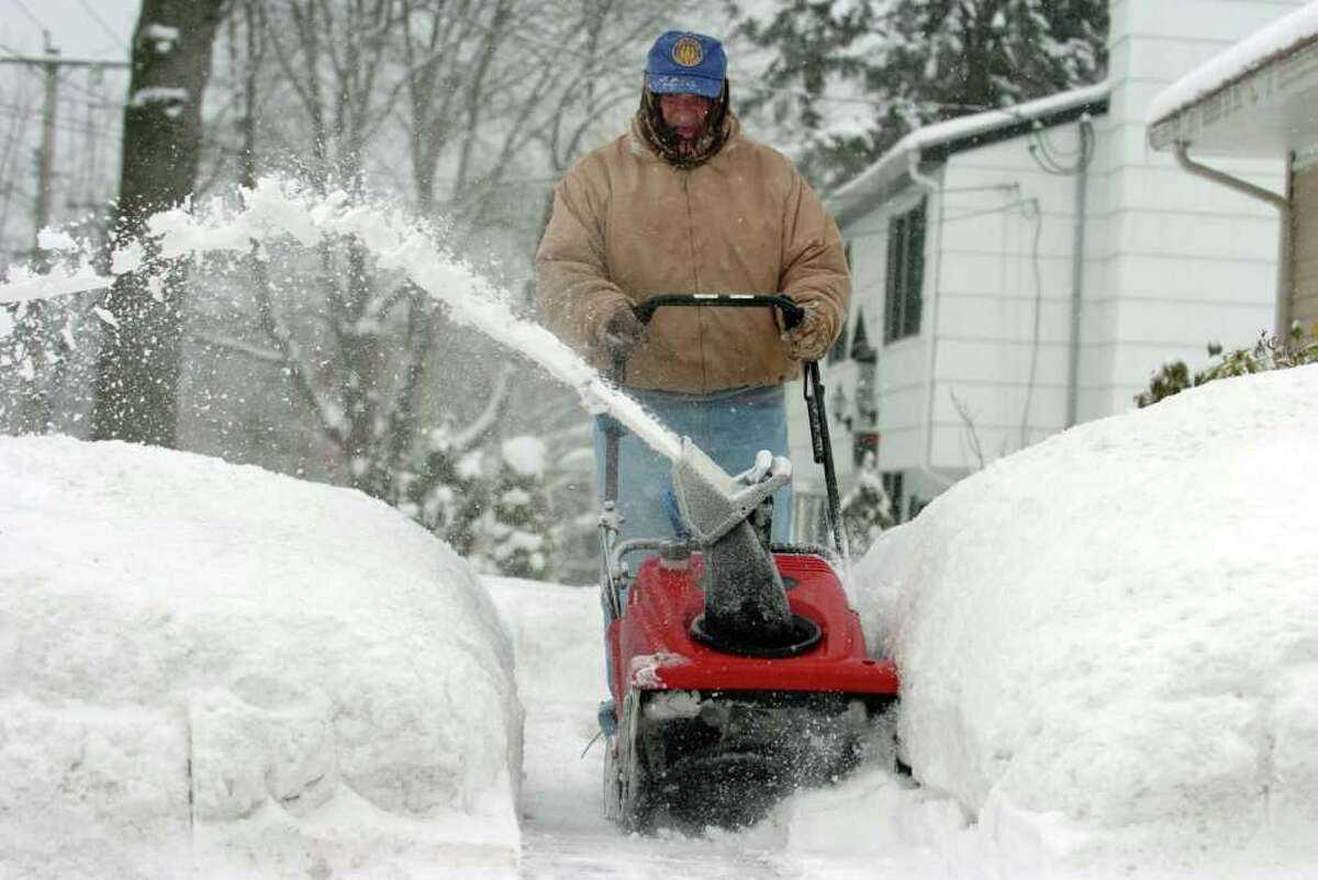 August Correia uses a snowblower to clear the walkway in front of his home in Milford, Conn. Wednesday, Jan. 26, 2011.