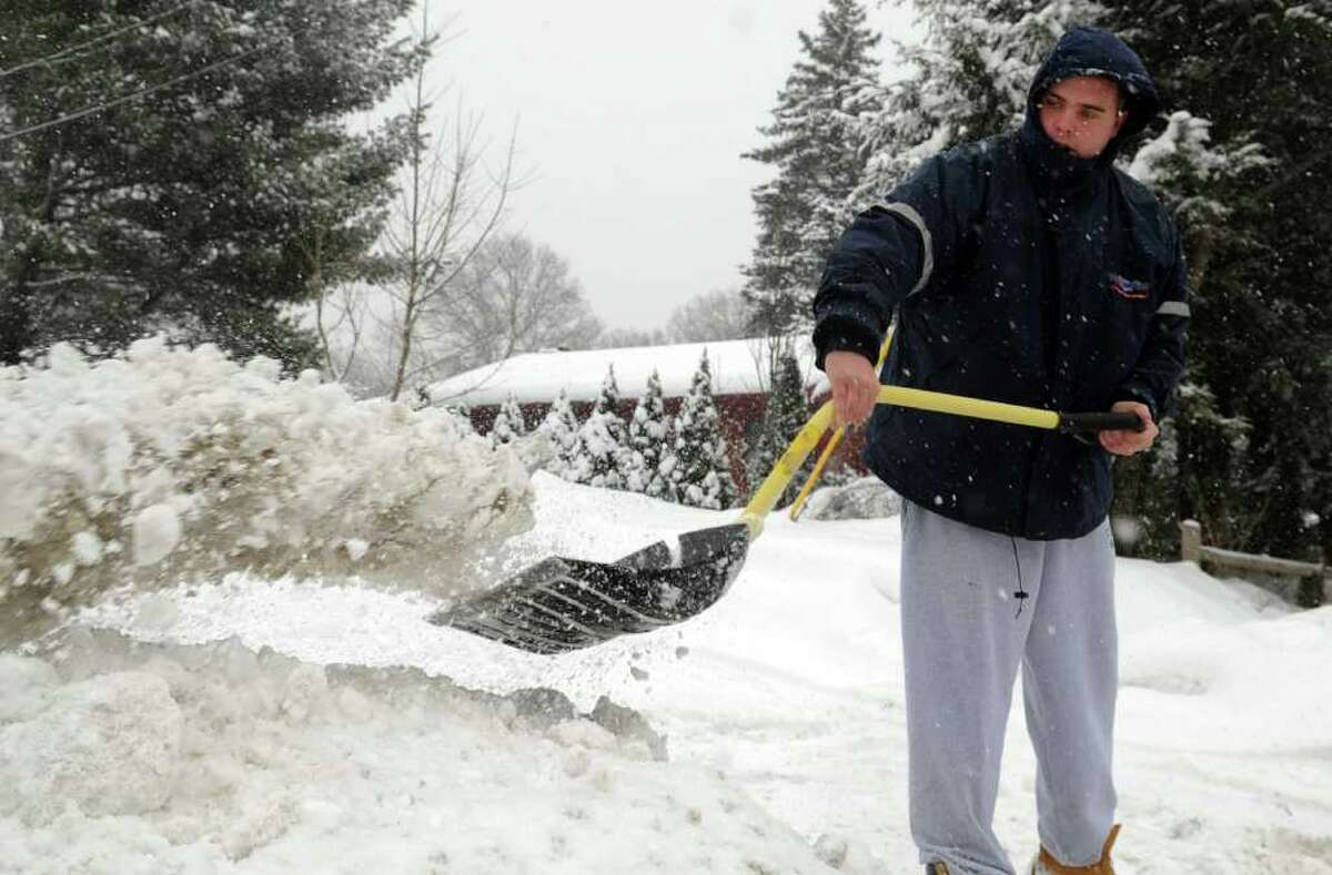 Gordon Stewart shovels the walkway in front of his home in Milford, Conn. Wednesday, Jan. 26, 2011.