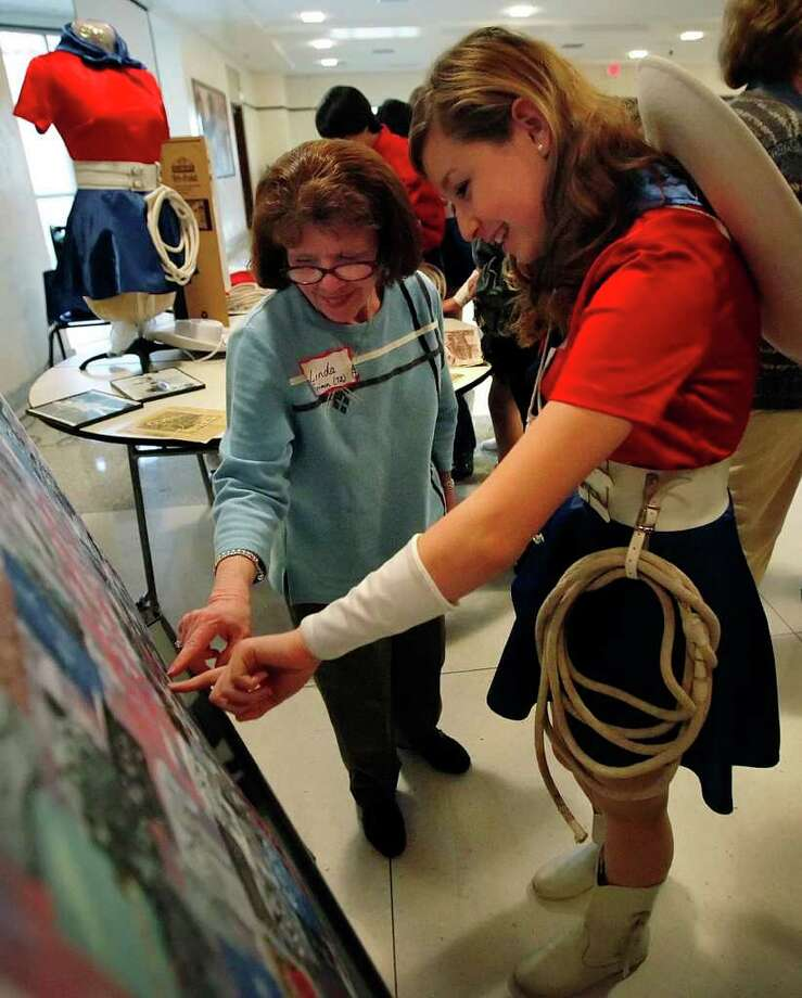 Jefferson High School Lassos alum Linda Grimm (left) and Destinee Salas marvel at a collage of images from years past after a Lasso Alumni Association event at the school in 2011. Photo: KIN MAN HUI, SAN ANTONIO EXPRESS-NEWS / San Antonio Express-News
