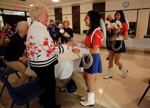 Lasso major Kymberlee Hernandez (center) and rope team captain Celena Garza (right) give a rose to Lasso alum Peggy Craig Mabry, class of 1947, at a recognition ceremony at Thomas Jefferson High School on Wednesday, Jan. 26, 2011.  Photo: KIN MAN HUI, SAN ANTONIO EXPRESS-NEWS / San Antonio Express-News