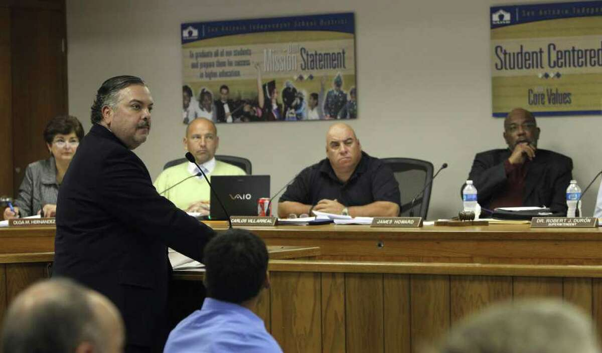 Henry Muñoz III (standing, left) makes a presentation to the SAISD board. In a controversial decision, his Kell Muñoz firm and its partner Jacobs won the $12.5 million contract.