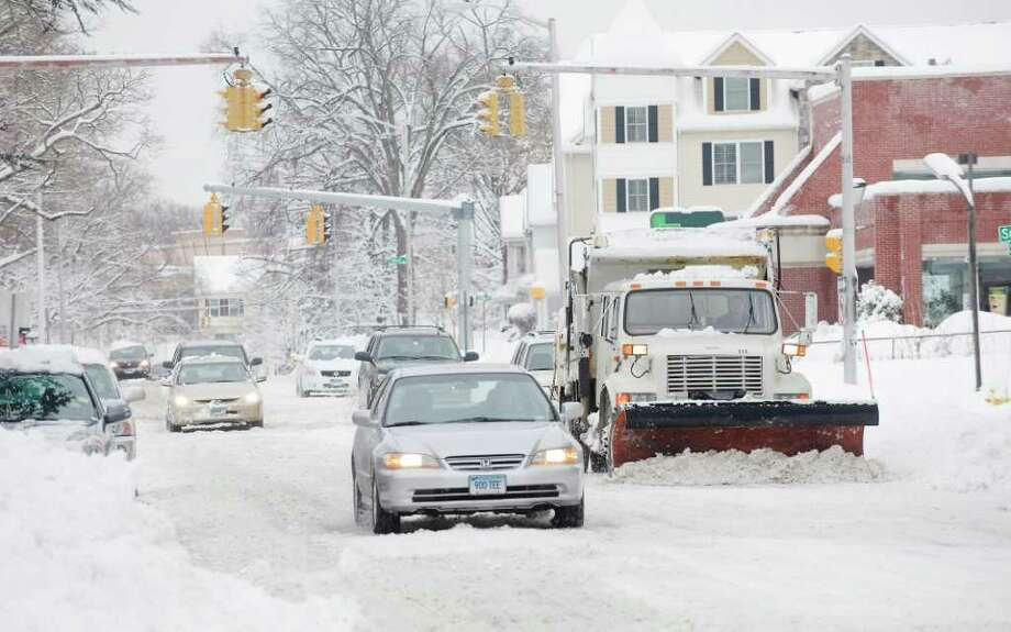 Drivers share the road with city plows during the morning commute on Summer St. in Stamford, Conn. on Thursday January 27, 2011. Photo: Kathleen O'Rourke, Stamford Advocate / Stamford Advocate