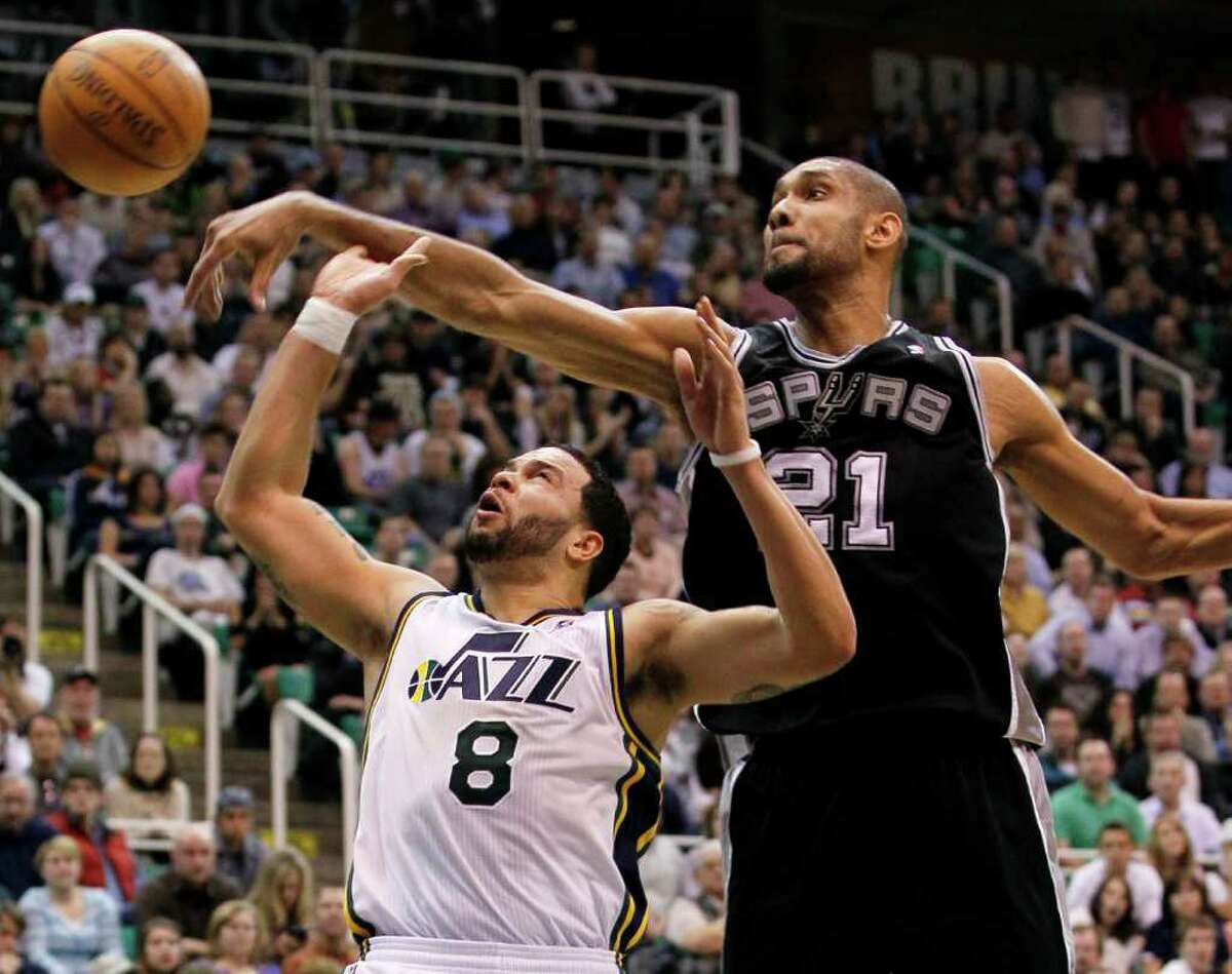 Spurs center Tim Duncan (21) knocks the ball away from Jazz guard Deron Williams (8) during the second half of an NBA basketball game in Salt Lake City, Wednesday Jan. 26, 2011. The Spurs defeated the Jazz 112-105.
