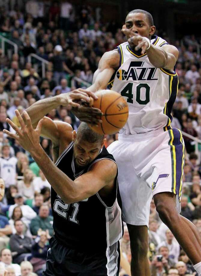 Jazz forward Jeremy Evans (40) grabs a rebound away from Spurs center Tim Duncan (21) during the second half of an NBA basketball game in Salt Lake City, Wednesday Jan. 26, 2011. The Spurs defeated the Jazz 112-105. Photo: AP