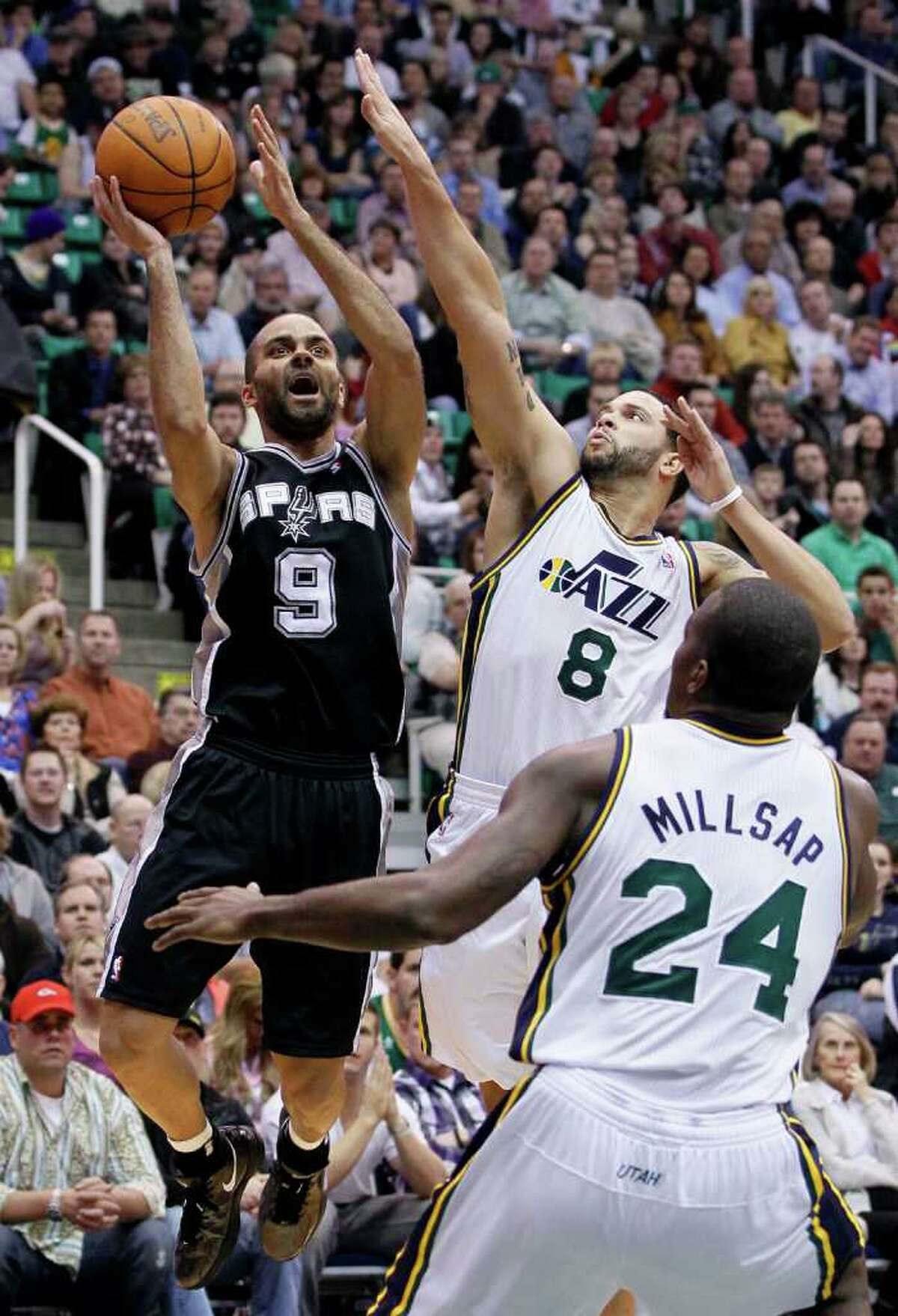 Spurs guard Tony Parker (9) attempts to score as Jazz guard Deron Williams (8) and forward Paul Millsap (24) defend during the first half of an NBA basketball game in Salt Lake City, Wednesday Jan. 26, 2011.