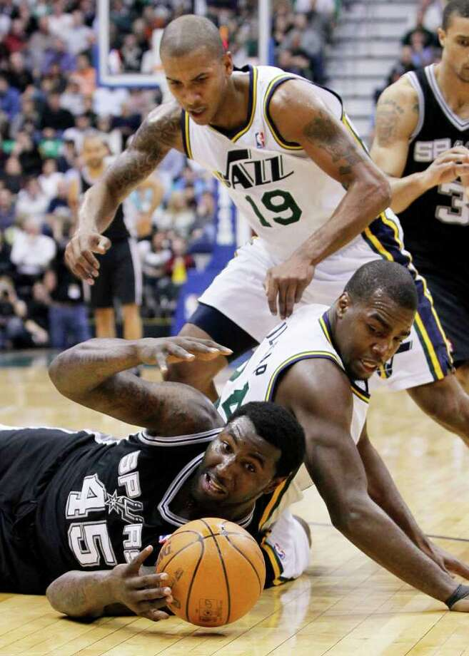 Spurs forward DeJuan Blair (45) Jazz forward Paul Millsap (24) and Jazz guard Raja Bell (19) go after a loose ball during the first half of an NBA basketball game in Salt Lake City, Wednesday Jan. 26, 2011. Photo: AP