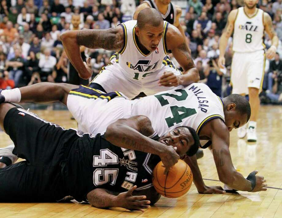 Spurs forward DeJuan Blair (45) and Jazz forward Paul Millsap (24) fall to the court while going after a loose ball as Jazz guard Raja Bell (19) assists during the first half of an NBA basketball game in Salt Lake City, Wednesday Jan. 26, 2011. Photo: AP