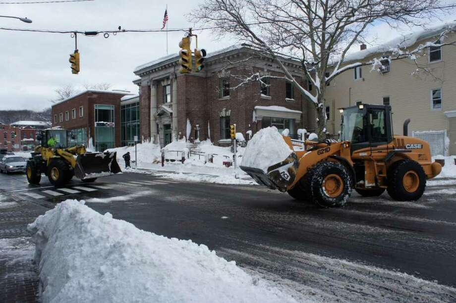 Payloaders move mountains of snow from Post Road East in downtown Westport on Thursday morning. Photo: Paul Schott / Westport News