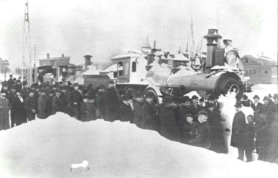 The Great Blizzard of 1888 dropped an estimated 40 inches of snow, accompanied by winds gusting up to 70 mph, as it roared through the area on March 12 and even halted rail traffic. Here town residents gather around a snow-covered train in Greenwich. Photo courtesy of the Greenwich Historical Society. Photo: Contributed Photo, ST / Greenwich Time Contributed