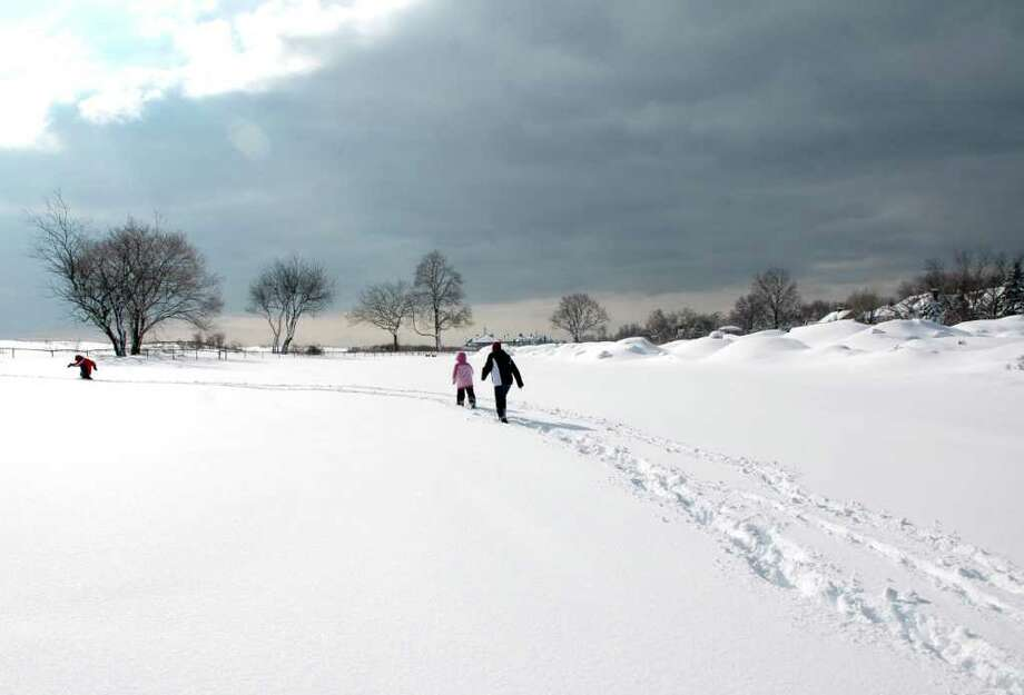 Alex and Lauren Bratton walk through the snow with their grandmother, Arlene Poucher towards the water at Jennings Beach in Fairfield, Conn. on Thursday, Jan. 27, 2011. Photo: Cathy Zuraw / Connecticut Post