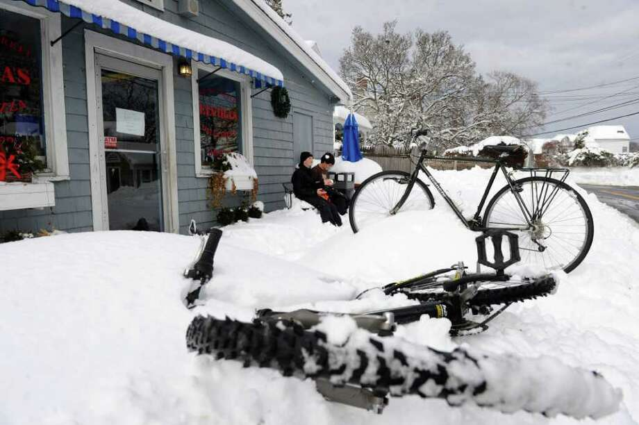 Matteo Bruni, 13, right, and Thomas Rosiello, 12, left, sit outside Elvira's Pizza and Deli after riding their bikes to the shoreline in the snow in Westport Thursday, January 27, 2011. Photo: Lindsay Niegelberg / Connecticut Post