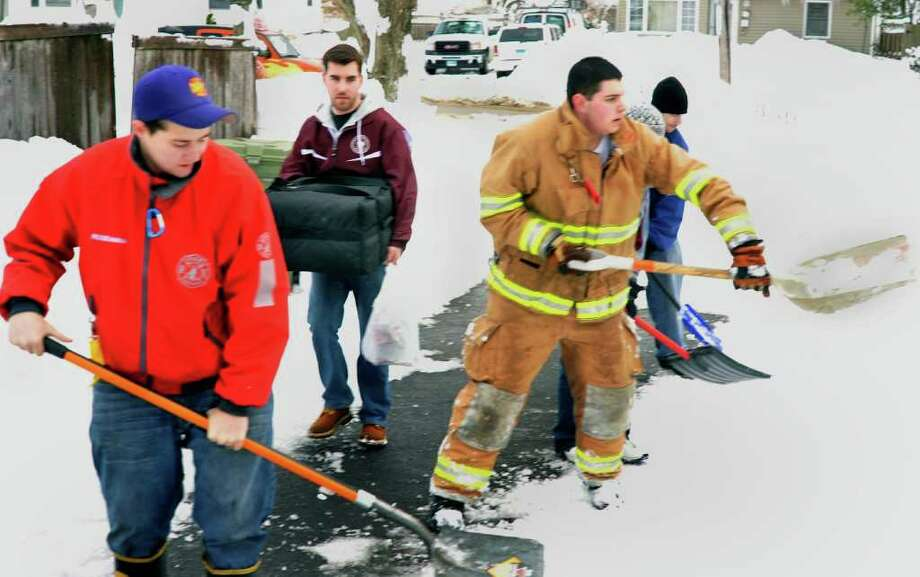 Ross Bassett of Famous Pizza in Bethel, delivers an order to Jeannine Bruey's Bethel home Thursday, Jan. 27, 2011. Bethel volunteer firefighters, including Roseanna Burtos, left, and Ryan McNair, right, help shovel Bruet's walkway. Photo: Michael Duffy / The News-Times