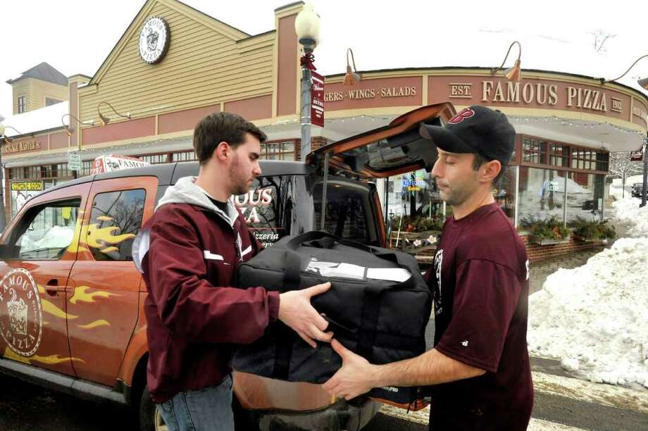 Ross Bassett takes hold of pizzas from Perry Anastasakis outside of Famous Pizza in Bethel. Famous Pizza is participating in Bethel Restaurant Week. Photo: Michael Duffy / The News-Times