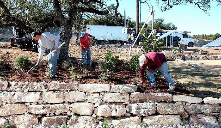 Land Design employees put mulch around the Texas native plants at the BuiltSmart Resources Net Zero Green Show Home. The model home and education center is off U.S. 281, at 2614 E. Ramblewood St., and opens to the public today. EDWARD A. ORNELAS/eaornelas@express-news.net