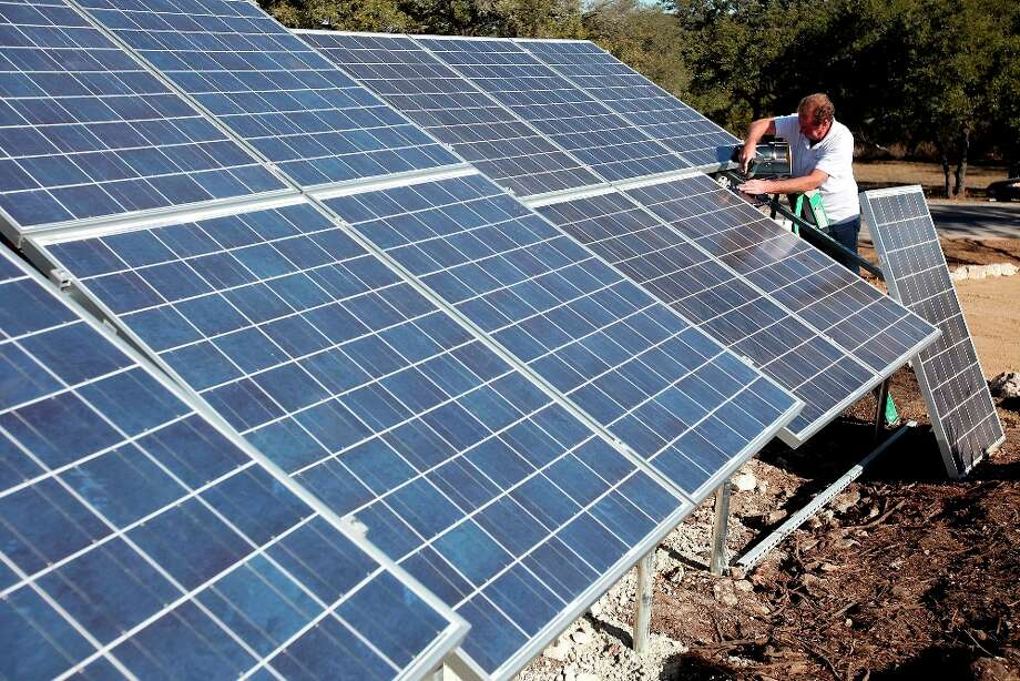 BuiltSmart Solar President Al Unsinn works on solar panels outside the home. The array is expected to produce slightly more energy than a family of five would use in a year.  EDWARD A. ORNELAS/eaornelas@express-news.net