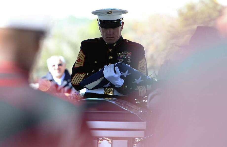 Master Sgt. Ronald Taylor of the 4th Reconnaissance Battalion holds one of four flags presented to family members of Marine Sgt. Wesley Rice during the funeral service for Rice at Fort Sam Houston National Cemetery. Photo: KIN MAN HUI, SAN ANTONIO EXPRESS-NEWS / San Antonio Express-News