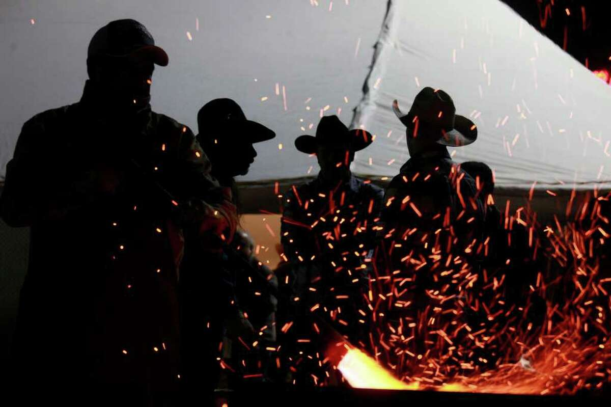 metro - Ruben Ramos, from left, tends to the fire while Teddy Lorentz, Wilson Gregory and Taylor Wimberley, all volunteers, talk during the Cowboy Breakfast at Cowboys Dance Hall on Friday, January 28, 2011. LISA KRANTZ/lkrantz@express-news.net