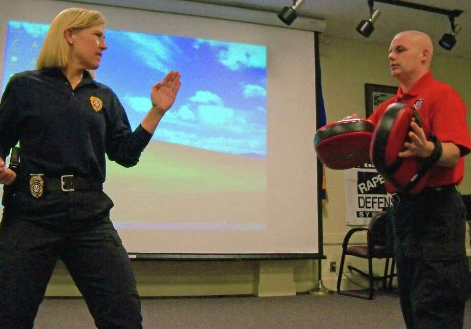 Fairfield Det. Beth Irizarry, left, and Fairfield University Sgt. Robert Didato demonstrate some of the techinques women are taught in the Rape Agression Defense course. Photo: Genevieve Reilly / Fairfield Citizen