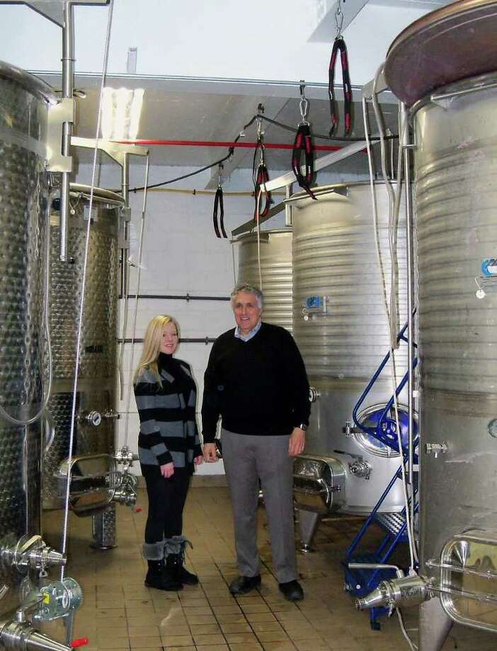 Jessica Beale, left, and Tony Izzo stand amid the large vats used to make wine for Black Rock Vintners, a winery in Bridgeport's Black Rock section owned by Izzo, a Fairfield resident. Photo: Genevieve Reilly / Fairfield Citizen