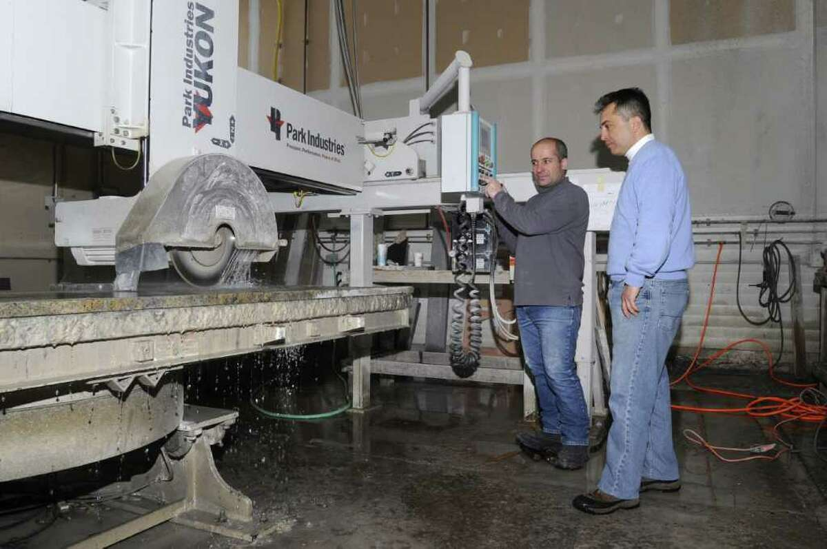 Academy Marble & Granite owner Sinan Sepkin, right, looks on as John Yuksel, left, cuts a large piece of granite with a bridge saw, at the fabrication facility in Bethel on Wednesday, Jan. 26, 2011.