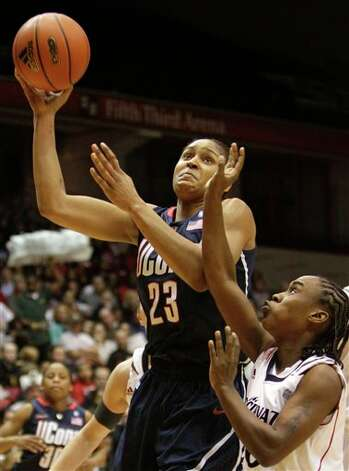 UConn forward Maya Moore (23) drives against Cincinnati guard Bjonee Reaves  in the first half of an NCAA college basketball game, Saturday, Jan. 29,  2011, in Cincinnati.