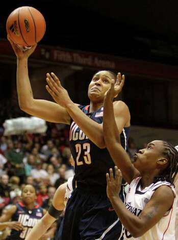 Connecticut forward Maya Moore (23) drives against Cincinnati guard Bjonee Reaves in the first half of an NCAA college basketball game, Saturday, Jan. 29, 2011, in Cincinnati. (AP Photo/Al Behrman) Photo: AP