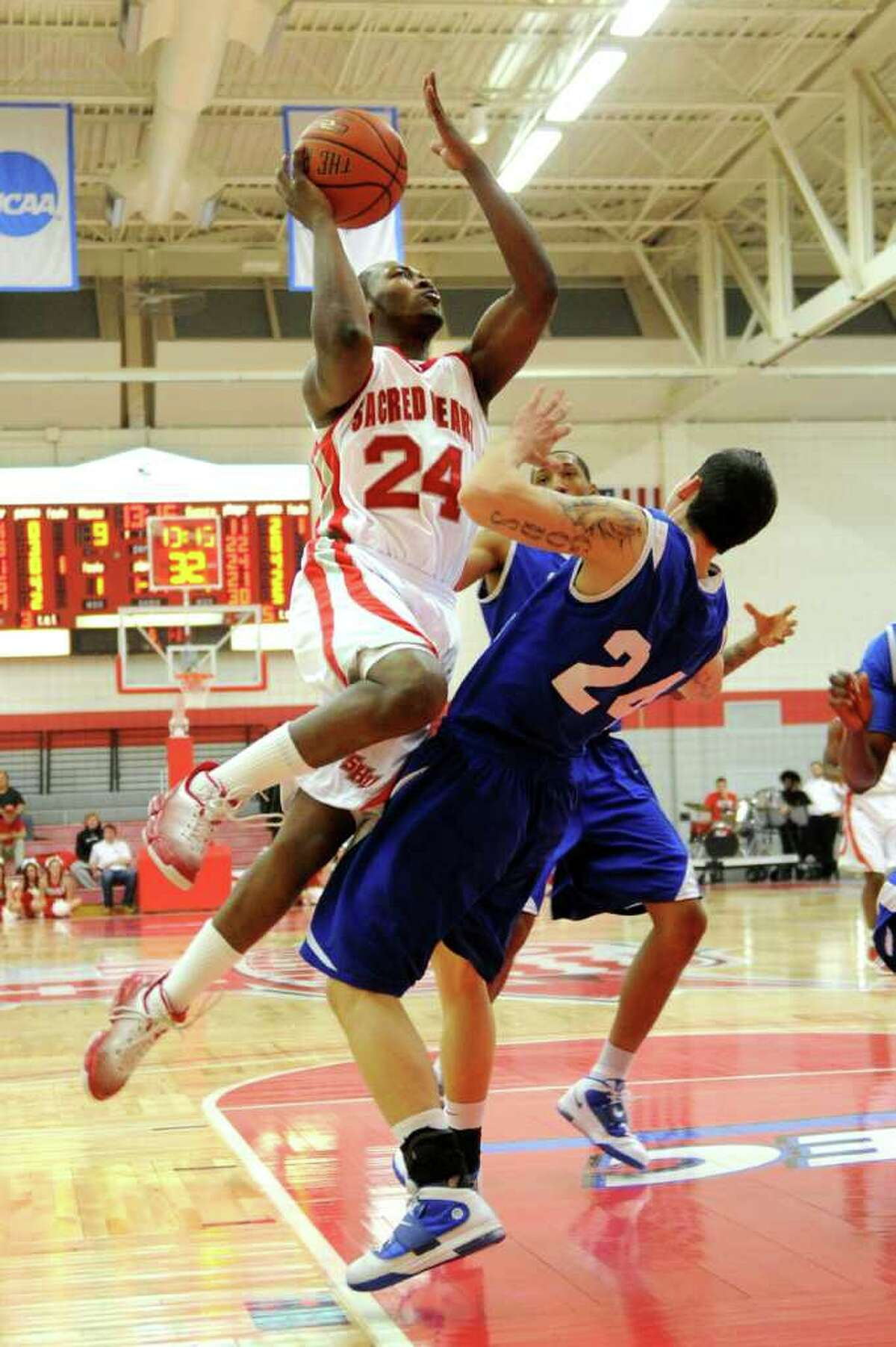Sacred Heart University's Chris Evans puts up a shot and fouls Robby Ptacek during Thursday's game against Central Connecticut State University in Fairfield on January 13, 2011.