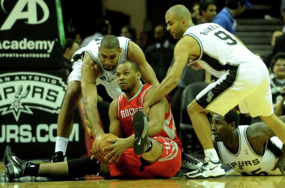 Chuck Hayes of the Houston Rockets looks to pass off as Tim Duncan, left, Tony Parker, (9) and DeJuan Blair of the San Antonio Spurs defend during NBA action at the AT&T Center on Saturday, Jan. 29, 2011. BILLY CALZADA / gcalzada@express-news.net