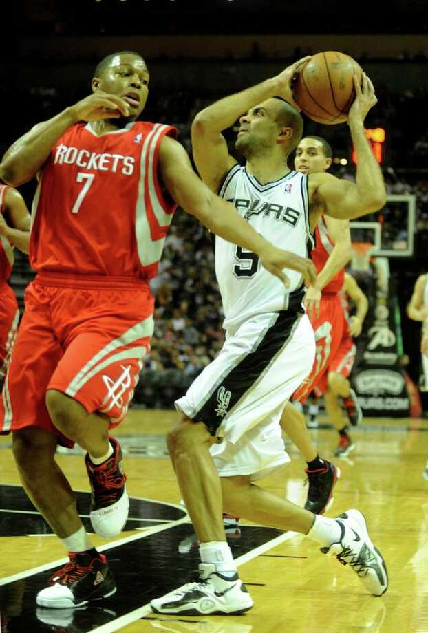 Tony Parker (9), drives to the basket behind Kyle Lowry (7) of the Houston Rockets during NBA action at the AT&T Center on Saturday, Jan. 29, 2011. BILLY CALZADA / gcalzada@express-news.net