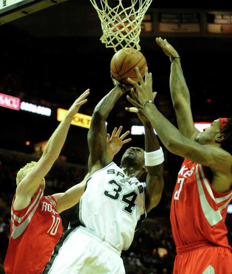Antonio McDyess (34) of the San Antonio Spurs penetrates to score as Chase Budinger (10) and Jordan HIll, right, of the Houston Rockets collapse on him during NBA action at the AT&T Center on Saturday, Jan. 29, 2011. BILLY CALZADA / gcalzada@express-news.net