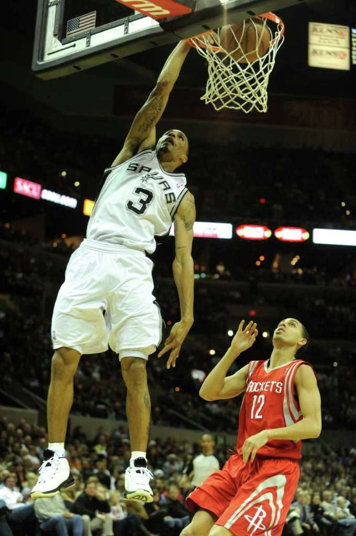 George Hill of the San Antonio Spurs dunks to end a breakaway as Kevin Martin of the Houston Rockets gives chase during NBA action at the AT&T Center on Saturday, Jan. 29, 2011. BILLY CALZADA / gcalzada@express-news.net Houston Rockets at San Antonio Spurs