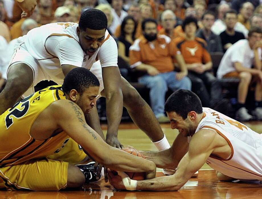 Missouri's Steve Moore (left) scrapes for a loose ball on the floor with Texas' Dogus Balbay (right) and Tristan Thompson during the first half. Photo: MICHAEL THOMAS/ASSOCIATED PRESS