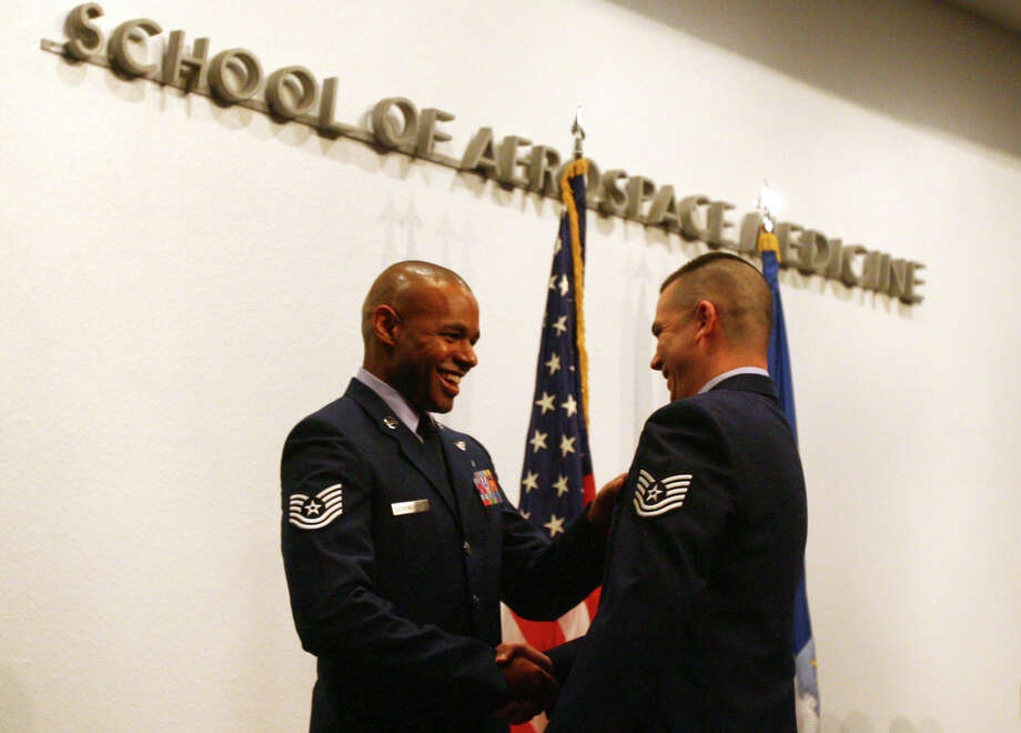 Tech. Sgt. Doug Gissendanner (left), the aeromedical evacuation technician course director, congratulates one of the graduates of Class 2011B during the final graduation ceremony for the School of Aerospace Medicine at Brooks City-Base. Photo: Jennifer Whitney/Special To The Express-News