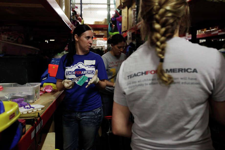 Laurie Butcher (left) and other Teach for America volunteers sort broken toys from the good ones at the Haven for Hope warehouse. About 60 volunteers from Teach for America went to the shelter to paint, landscape and perform chores. Photo: Jerry Lara/glara@express-news.net