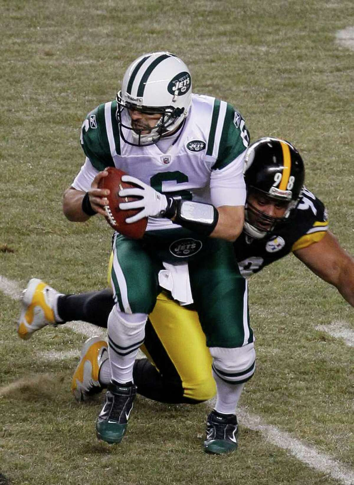 New York Jets quarterback Mark Sanchez avoids the rush by Pittsburgh Steelers defensive tackle Casey Hampton (98) during the first half of the AFC Championship NFL football game in Pittsburgh, Sunday, Jan. 23, 2011.