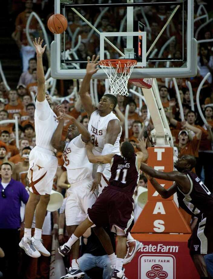 Texas players Gary Johnson (from left), Damion James, and Dexter Pittman jump to block a shot by Texas A&M's B.J. Holmes late in the Longhorns' 72-67 overtime victory over the Aggies on Jan. 16, 2010. Photo: Benjamin Sklar, Special To The Express-News / BENJAMIN SKLAR