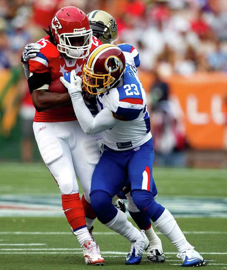 Kansas City Chiefs running back Jamaal Charles (25) of the AFC, center, is tackled by Washington Redskins cornerback DeAngelo Hall (23) of the NFC, right, and New Orleans Saints strong safety Roman Harper (41) during the second quarter of the NFL Pro Bowl football game, Sunday, Jan. 30, 2011 in Honolulu.  (AP Photo/ Marco Garcia) Photo: Marco Garcia, FRE
