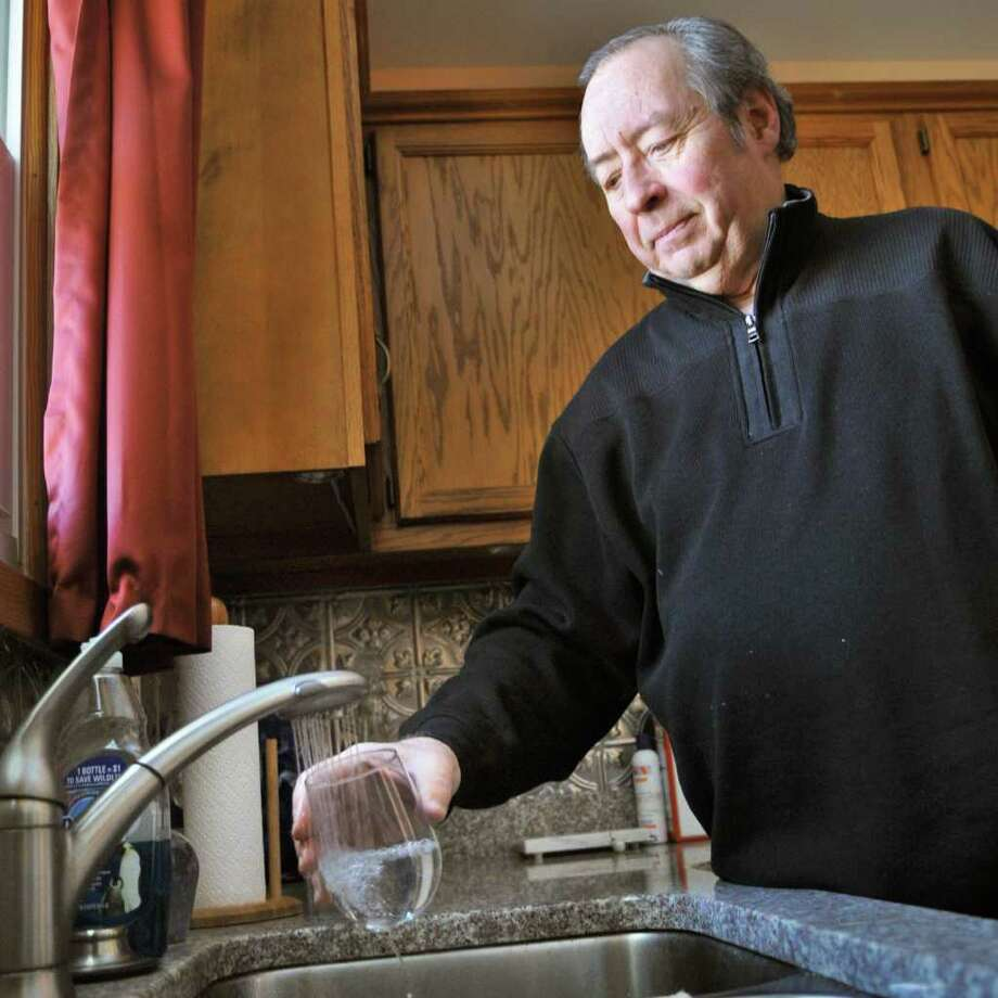 Eugene Booth pours a glass of water at his Troy home Thursday morning January 27, 2011.   (John Carl D'Annibale / Times Union) Photo: John Carl D'Annibale / 00011871A