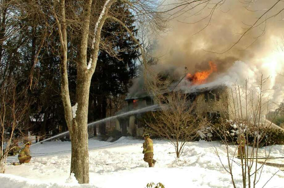 Firefighters battle a house fire at 1 Mill Road in Stamford, Conn. on Monday, Jan. 31, 2010. Photo: Dru Nadler / Stamford Advocate Freelance